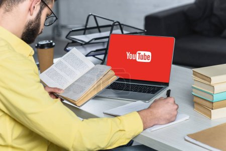 Photo pour Homme barbu étudiant avec livre près d'un ordinateur portable avec site youtube à l'écran dans le bureau moderne - image libre de droit