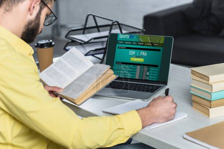 Photo for Bearded man studying with book near laptop with sportsbet website on screen in modern office - Royalty Free Image