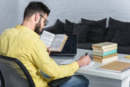 Photo for Bearded man studying with book near laptop with blank screen in modern office - Royalty Free Image
