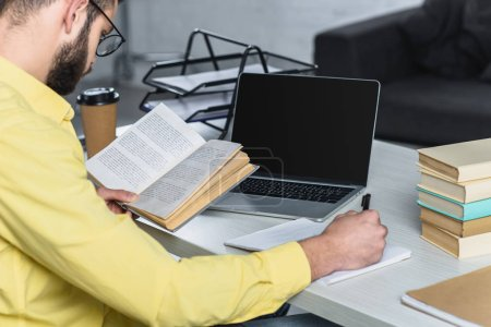 Photo for Man studying with book near laptop with blank screen in modern office - Royalty Free Image