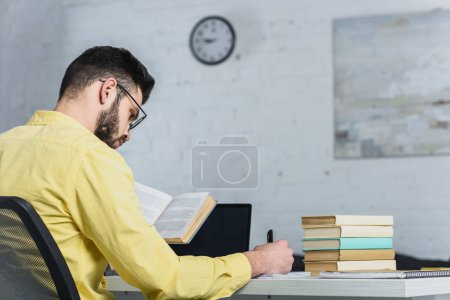 Photo for Selective focus of man writing while holding book in modern office - Royalty Free Image