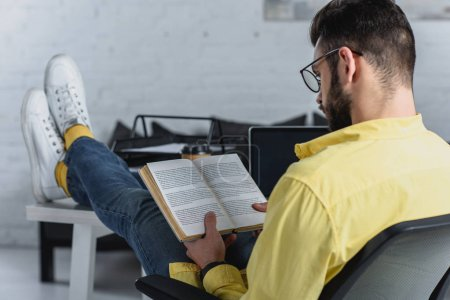 Photo for Selective focus of man studying with rook in modern office - Royalty Free Image