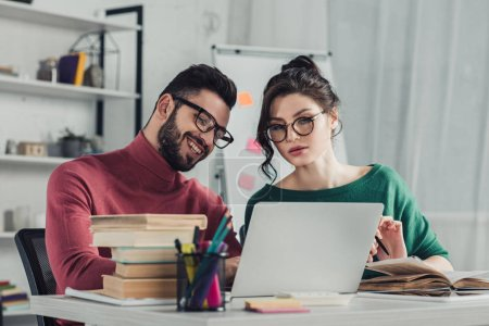 Photo for Cheerful man in glasses sitting near female colleague in modern office - Royalty Free Image
