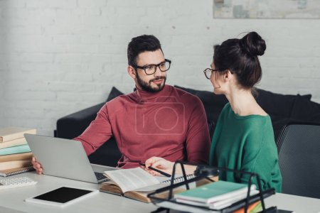 bearded man in glasses  looking at woman in modern office
