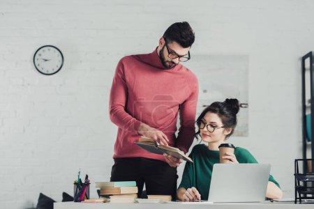 Foto de Guapo con barba hombre sosteniendo el libro junto a la mujer con la taza de papel - Imagen libre de derechos