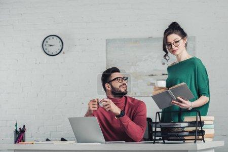 Foto de Hombre alegre en gafas mirando a mujer estudiando con el libro y sosteniendo la Copa con la bebida - Imagen libre de derechos
