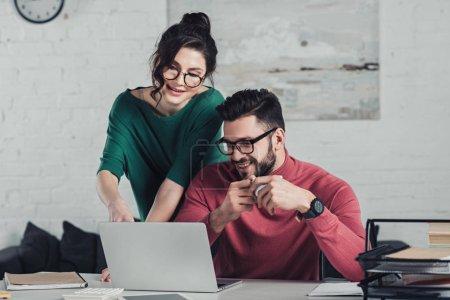 Foto de Alegres compañeros de trabajo en gafas mirando portátil y sonreír en la oficina moderna - Imagen libre de derechos