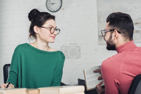 selective focus of attractive woman in glasses looking at bearded man holding book
