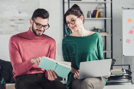 Photo for Cheerful woman with laptop looking at happy bearded man studying with book - Royalty Free Image