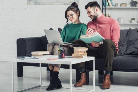 Photo pour Homme gai regardant ordinateur portable près de la femme dans des lunettes - image libre de droit