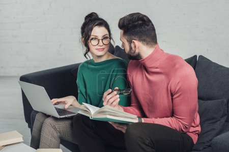 man looking at cheerful woman in glasses sitting with laptop