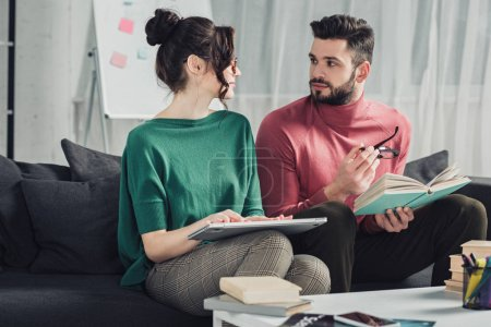 handsome bearded man looking at woman with laptop