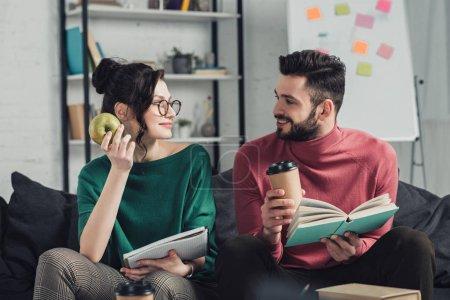Foto de Mujer feliz en gafas mirando barbudo a hombre mientras apple de explotación de la mano - Imagen libre de derechos