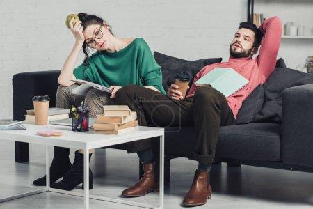 Photo pour Femme dans les verres, tenant la pomme dans la main et assis près de l'homme fatigué avec la tasse de papier - image libre de droit