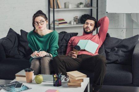Photo pour Femme s'ennuie dans les verres, tenant le cahier et crayon tout en restant assis près de bel homme - image libre de droit