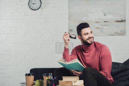 Photo pour Bel homme barbu étudie avec le livre et la tenue des lunettes en mains - image libre de droit