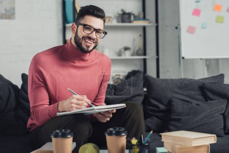 Photo for Cheerful man in glasses writing in notebook at home - Royalty Free Image