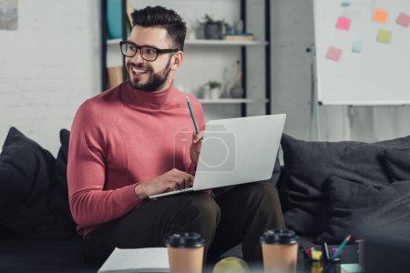 Photo pour Joyeux barbu homme dans des verres à l'aide d'ordinateur portable tout en étant assis sur le canapé - image libre de droit