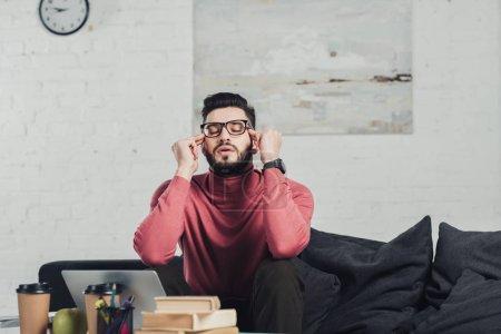 hombre guapo en gafas sentado cerca del ordenador portátil en el sofá