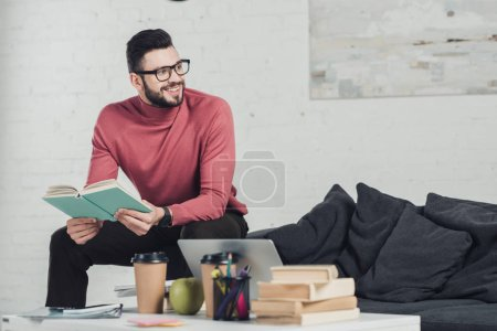 Photo for Cheerful man in glasses sitting near laptop and holding book - Royalty Free Image