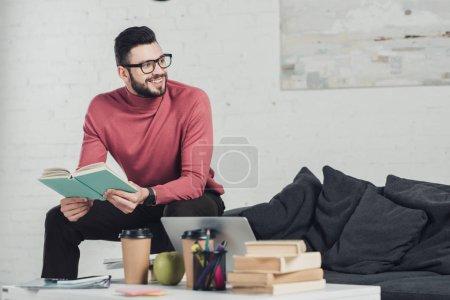 Photo pour Homme gai dans des verres, assis près d'ordinateur portable et la tenue de livre - image libre de droit