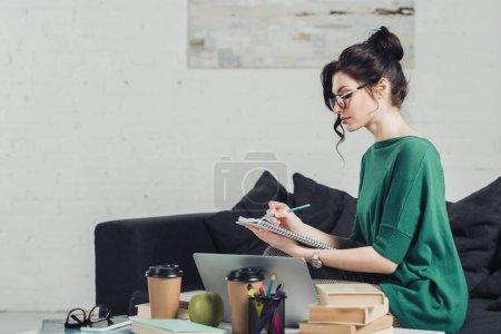 Photo pour Jolie femme à lunettes écrire dans cahier pendant ses études à la maison - image libre de droit