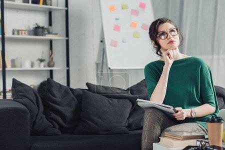Photo pour Femme réfléchie dans des lunettes tenant un cahier et assis sur le canapé à la maison - image libre de droit