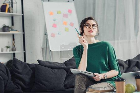 Photo pour Femme chère dans des lunettes tenant un cahier et assis sur le canapé à la maison - image libre de droit