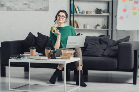 Photo for Attractive woman in glasses holding apple while sitting with laptop on sofa - Royalty Free Image