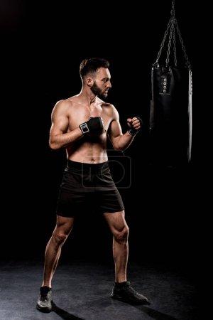 Photo for Handsome boxer kicking boxer bag on black background - Royalty Free Image