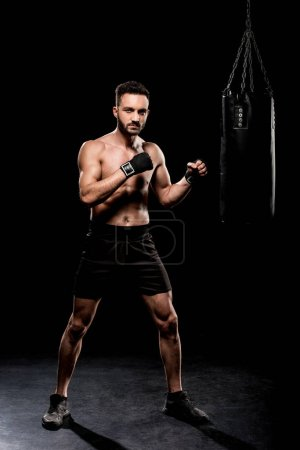 Photo for Handsome boxer looking at camera near boxer bag on black background - Royalty Free Image