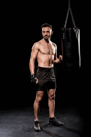 Photo for Handsome boxer standing near boxer bag on black background - Royalty Free Image