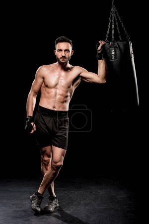 Photo for Handsome boxer standing with crossed legs near punching bag on black background - Royalty Free Image