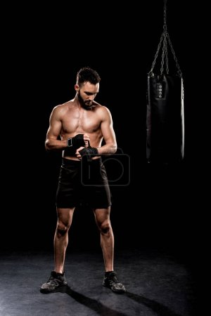 Photo for Shortless boxer standing near punching bag on black background - Royalty Free Image