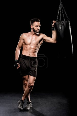 Photo for Shortless boxer standing with crossed legs near punching bag on black background - Royalty Free Image
