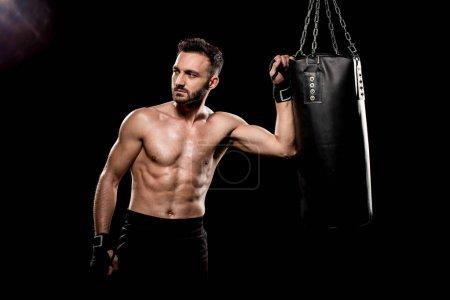 Photo pour Boxer dénudé, debout près de sac de boxe isolé sur fond noir - image libre de droit