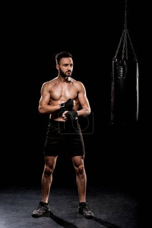 Photo for Muscular shortless boxer standing near punching bag on black background - Royalty Free Image