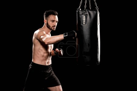 Photo for Muscular boxer hitting punching bag isolated on black - Royalty Free Image