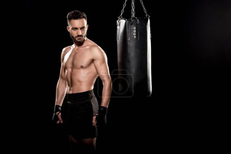 Photo for Muscular shortless boxer looking at punching bag isolated on black - Royalty Free Image