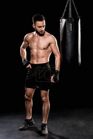 shortless bearded man looking at punching bag on black background