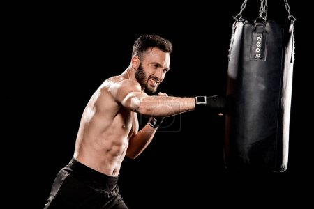 Photo for Shortless bearded man exercising with punching bag isolated on black - Royalty Free Image