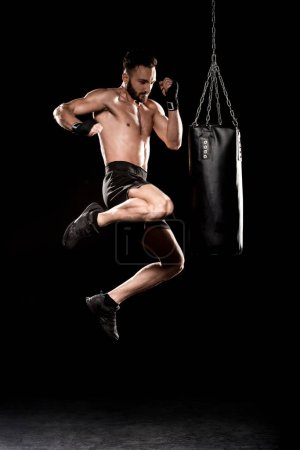 Photo for Handsome boxer performing flying kick near punching bag on black background - Royalty Free Image