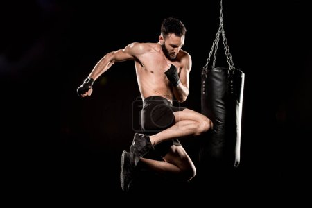 Photo for Shortless boxer performing flying kick near punching bag isolated on black - Royalty Free Image