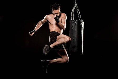 Photo pour Athlète dénudé effectuant le coup de pied volant près de sac de boxe isolé sur fond noir - image libre de droit