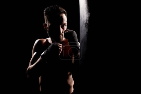 Photo for Shortless athlete hitting punching bag isolated on black - Royalty Free Image