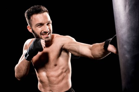 Photo pour Dénudé sportif coup de sac de boxe isolé sur fond noir - image libre de droit
