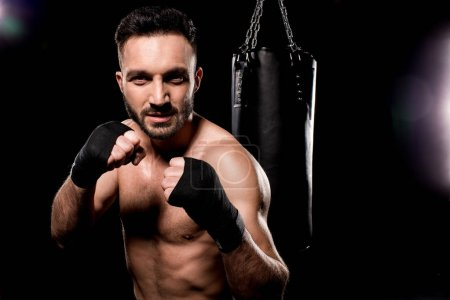 Photo for Shortless sportsman looking at camera and standing in boxing pose on black background - Royalty Free Image