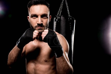 Photo for Handsome sportsman standing in boxing pose on black background - Royalty Free Image