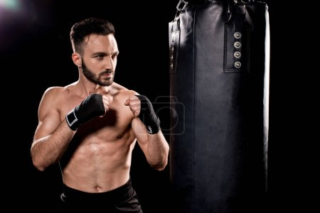 Photo for Handsome sportsman standing in boxing pose and looking at punching bag on black background - Royalty Free Image