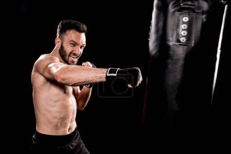 Photo pour Beau sportif coup de sac de boxe isolé sur fond noir - image libre de droit